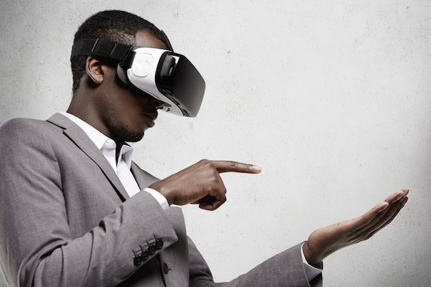 Profile of african businessman in gray suit wearing 3d headset glasses in office, gesturing as if holding some gadget on his palm and touching it with his index finger while playing video games