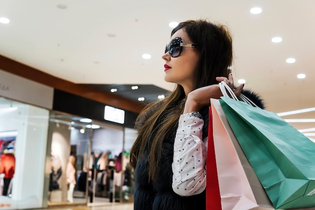 Profile of attractive lady in glasses and fur waistcoat holding many shopping bags at mall background. girl with packages walking in department store. feeling satisfaction after expences. sideview.