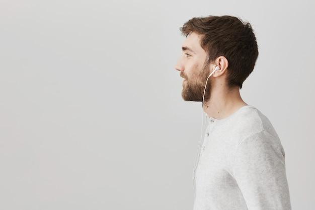 Profilo del bel ragazzo barbuto ascoltando musica in auricolari
