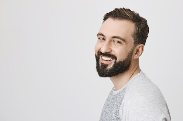 Profilo di uomo barbuto con nuovo taglio di capelli, sorridente