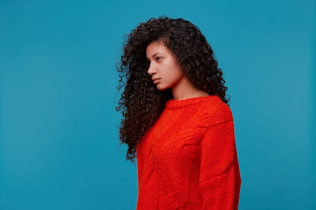 Profile of beautiful hispanic latino girl woman with serious stern look, long dark curly wavy hair in red sweater standing isolated over blue studio wall looking away