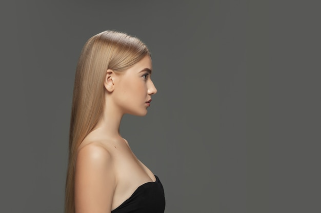 Profile. beautiful model with long smooth, flying blonde hair on dark grey studio background. young caucasian model with well-kept skin and hair blowing on air. concept of salon care, beauty, fashion.