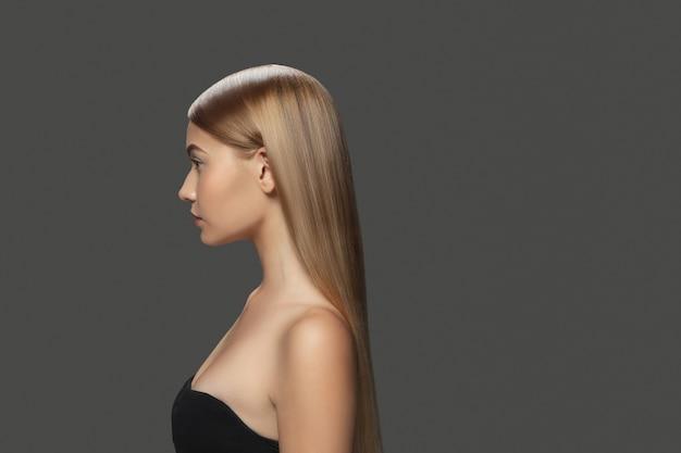プロフィール。ダークグレーのスタジオの背景に長く滑らかな、飛んでいるブロンドの髪を持つ美しいモデル。手入れの行き届いた肌と髪の毛が空気を吹き込んでいる若い白人モデル。サロンケア、美容、ファッションのコンセプト。