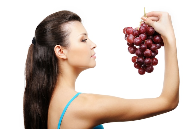 Profile of beautiful young girl holding bunch of grapes