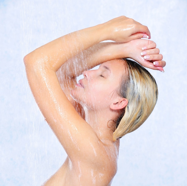 Profile of beautiful young girl taking shower