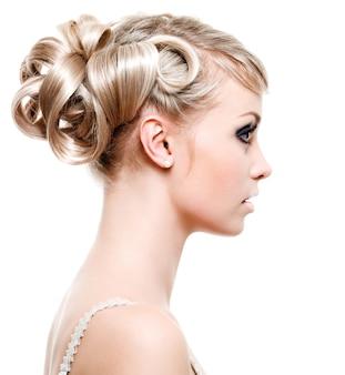 Profilo di bella giovane donna con l'acconciatura di moda - su uno spazio bianco