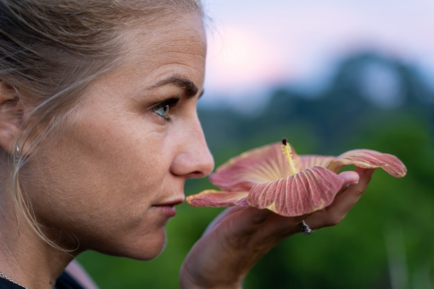 Profile of a blonde girl with blue eyes smelling an exotic flower