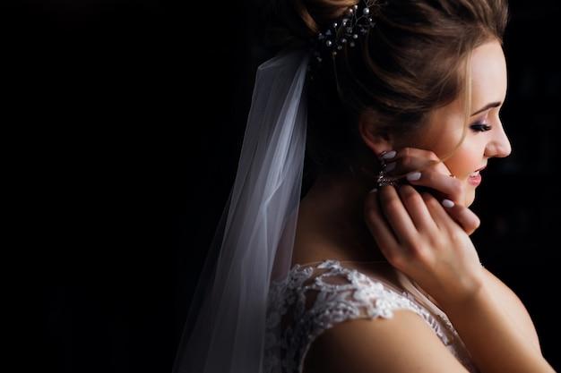 結婚式のベールと白いドレスのプロファイルの花嫁。女の子はイヤリングを修正します。閉じる。