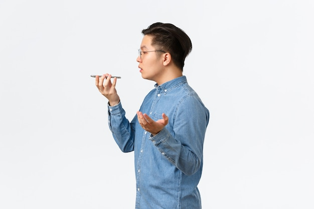 Profile of busy young asian male entrepreneur, freelancer record voice message, talking into phone speaker, making notes on recorder, having conversation, standing white background