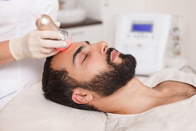 뷰티 클리닉에서 rf 리프팅 치료를 즐기는 수염 난 남자의 프로필 닫기