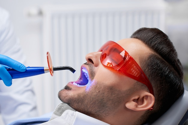 Profile close up shot of a handsome bearded man wearing protective glasses getting teeth filling done at his dental clinic copyspace technology ultraviolet uv lamp modern medicine health.