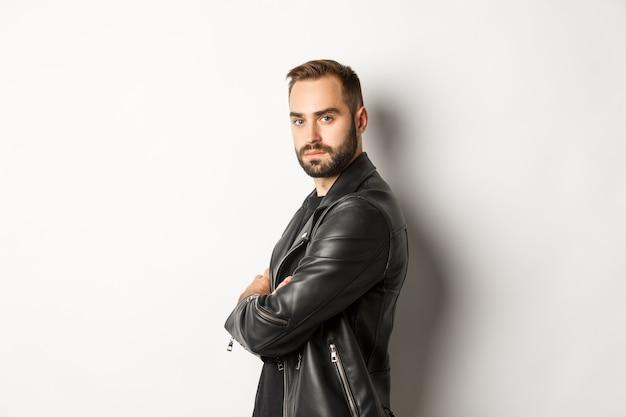 Profilo di uomo barbuto fiducioso e bello in giacca di pelle nera, gira la faccia alla telecamera e sembra serio