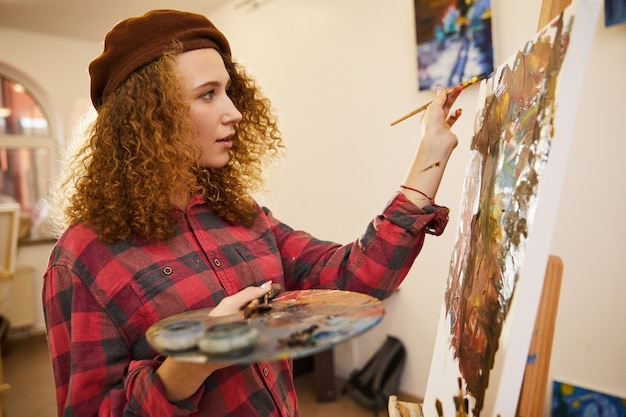 Profile of curly artist during her work