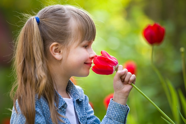 Profile of cute pretty smiling child girl with gray eyes and long hair smelling bright red tulip flower on blurred sunny summer green bokeh background.