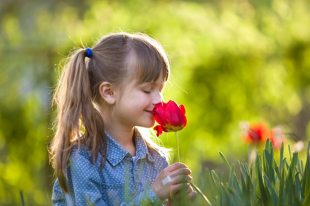 Profile of cute pretty smiling child girl with gray eyes and long hair smelling bright red tulip flower