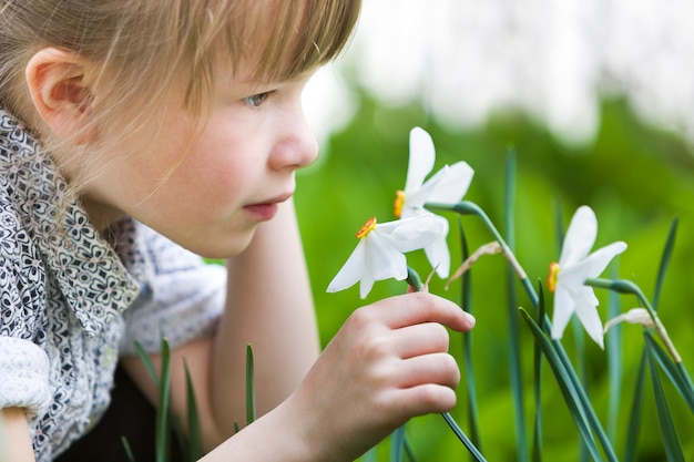 Profile of cute pretty thoughtful child girl outdoor smelling white daffodil on sunny summer or spring day.