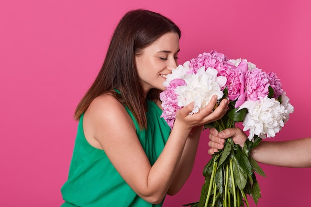 Profile of cute smiling girl with closed eyes smelling flowers with colorful petals, touching them with both hands, being in high spirits, unknown hand holding bouquet isolated over pink