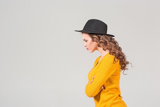 Il profilo della ragazza emotiva in cappello sulla parete grigia dello studio