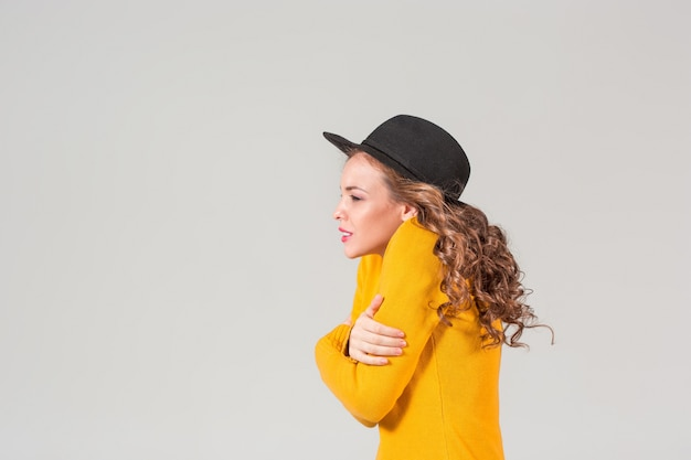 The profile of emotional girl in hat on gray  wall