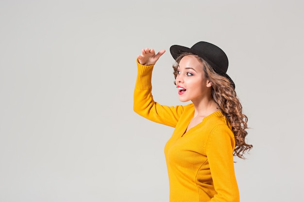Il profilo della ragazza emotiva con cappello su grigio