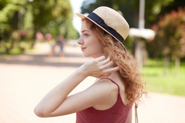 Profile of european romantic attractive young female looking aside, touching her hair with fingers, wearing straw hat and red shirt, being fond of accessories, having sincere smile on her face.