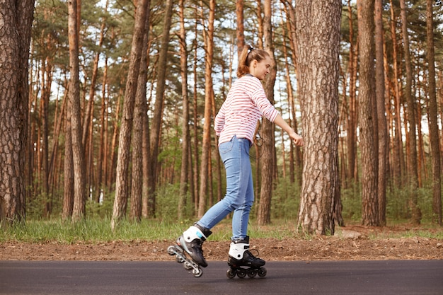 Profile of experienced skilled active young woman rollerskating with pleasure, being on road near forest, sticking to healthy lifestyle, having around headphones, wearing striped sweatshirt and jeans.