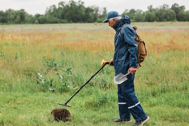 金属探知機とシャベルを使って、野原や牧草地の地面にある歴史的遺物やコインを探す、集中したトレジャー ハンターの全長屋外ショットのプロフィール