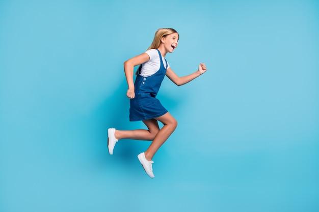 Профиль полноразмерной фотографии веселой смешной блондинки, прыгающей, кричащей, носить футболку, платье, кроссовок, изолированную на пастельно-синем цветном фоне
