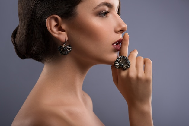 Profile of a gorgeous elegant female fashion model shushing with her finger to her lips