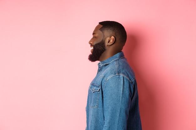 Profilo di bel ragazzo nero barbuto in piedi su sfondo rosa, sorridente e guardando a sinistra lo spazio della copia.
