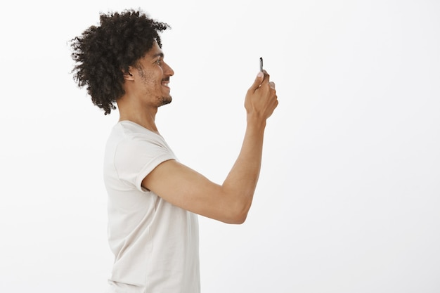 Profile of handsome black man taking picture of something on smartphone, photographing on phone