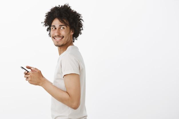 Profilo di bell'uomo nero girarsi e sorridere mentre si utilizza lo smartphone