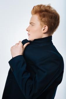 프로필. 재킷을 입고 그 앞에서보고 그의 재킷을 만지고 잘 생긴 돌이 많은 빨간 머리 젊은 남자