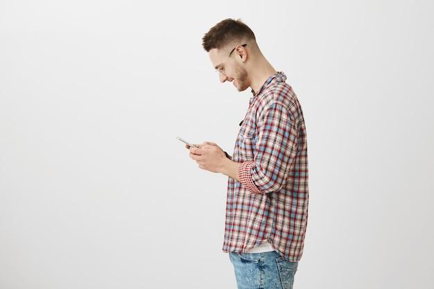 Profilo di bel ragazzo giovane in posa con il suo telefono