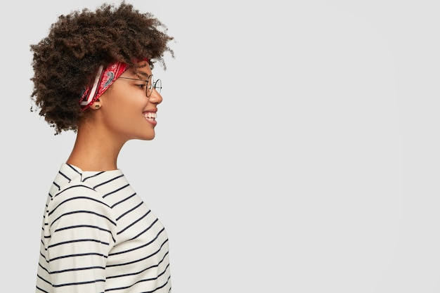 Profile of happy dark skinned girl wears striped clothes, headband, spectacles
