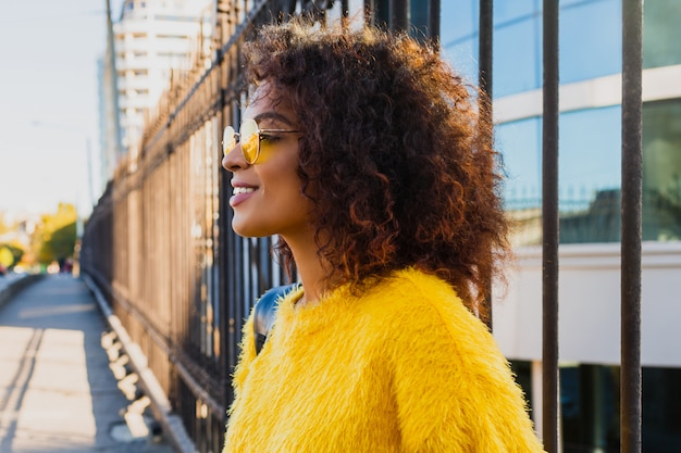 Profile of happy female with stylish hairstyle looking on horizon and dreaming