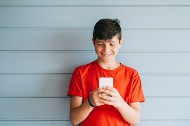 Profile of a happy male teen texting on a smart phone