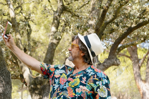 Profile of a man hat with a floral print shirt making a selfie in a garden