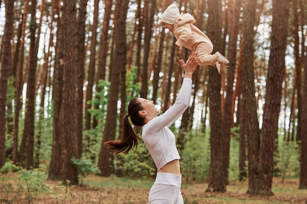 Profile of mother playing with baby girl, woman throwing up small daughter in air, happy family having fun outdoor