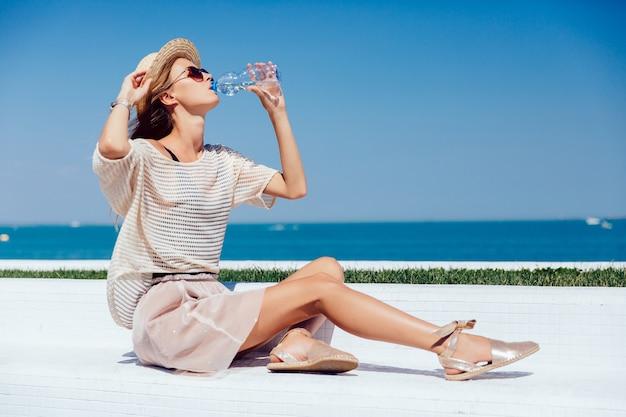 Профиль удивительной модели в солнцезащитных очках и шляпе, пить воду, сидя на скамейке