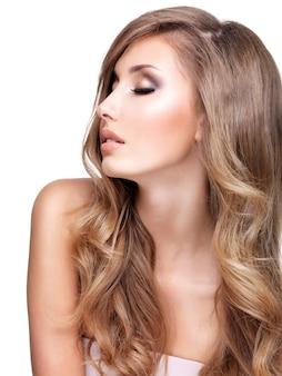 긴 물결 모양의 머리와 화장과 아름다운 젊은 여자의 프로필