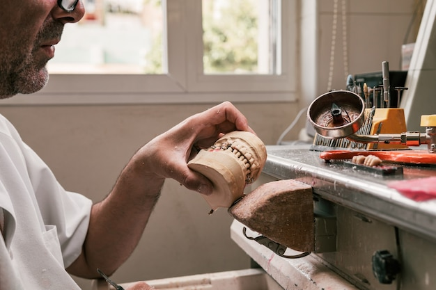 ワークショップで歯科補綴物の骨格を手に持っている歯科技工士のプロフィール