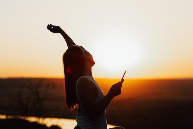 日没時の丘の上にヘッドフォンでスマートフォンで音楽を聴いて手を上げて幸せな女の子のプロフィール
