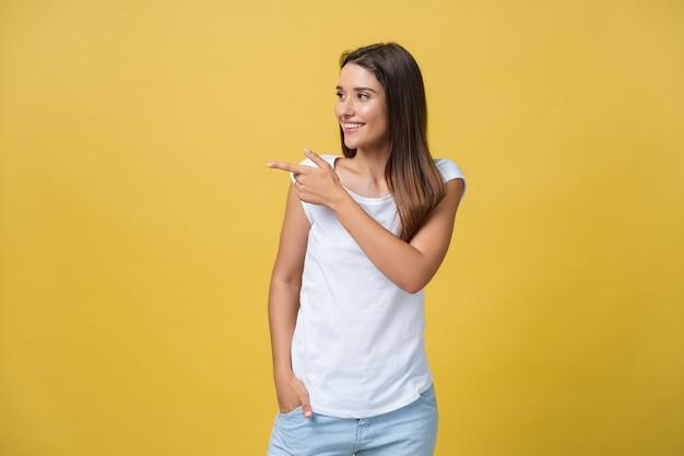 Профиль женщины указывая на космос экземпляра для рекламы изолированной на желтом фоне.