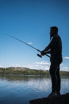 Профиль молодой азиатской рыбалки - азиатский мужчина с бородой и рубашкой, замаскированный в реке.