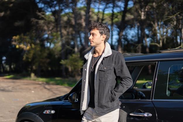 木々に囲まれた駐車場で車に横たわって冬のジャケットを着た若い男のプロフィール