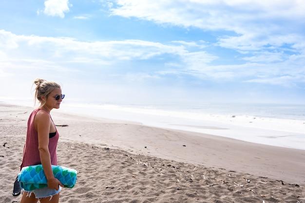 수평선을 바라보며 해변에 서 있는 젊은 여성의 프로필