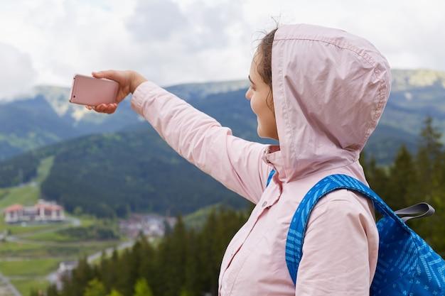 Профиль активного путешественника, делающего фотографии на фоне горы, записывающего видео для блога о путешествиях, проводящего время с удовольствием в отпуске, идущего в поход один, в теплой одежде.
