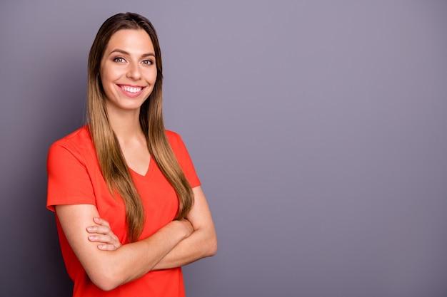 Профиль привлекательной бизнес-леди со скрещенными руками, зубастый улыбающийся ответственный человек в повседневной оранжевой футболке, изолированной серой стене