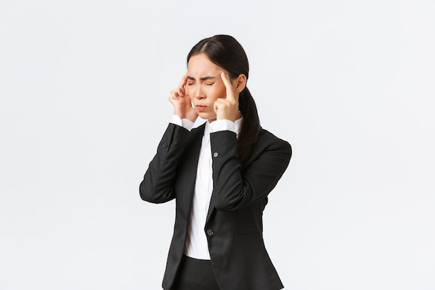 Профиль азиатской бизнес-леди в черном костюме, страдающей мигренью, касающейся висков и гримасой от болезненного ощущения в голове. женский офис-менеджер с головной болью, нуждается в обезболивающих, на белом фоне